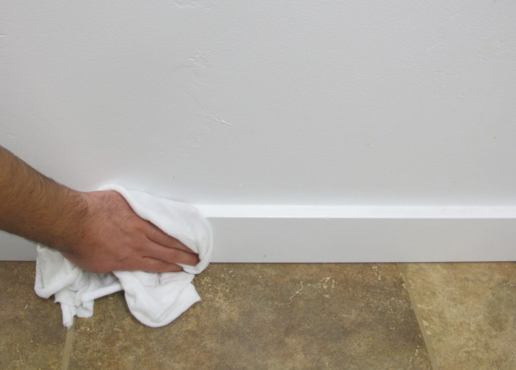 Wiping down a baseboard. 1024x734 - Dust & Debris: The Invisible Threats Of Your DIY Workspace