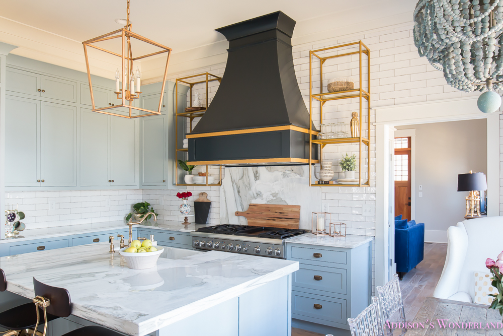 kitchen-white-marble-calcutta-gold-open-shelves-gold-black-vent-hood-blue-gray-cabinets-shaker-style